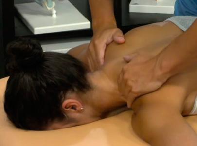 fisioterapeuta dando masaje en los hombros a una mujer