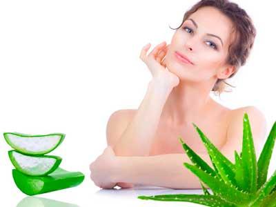 mujer con la piel clara y rodeada de la planta de aloe vera