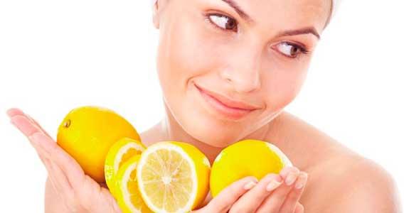 mujer con varios limones que sirven para aclarar la piel naturalmente