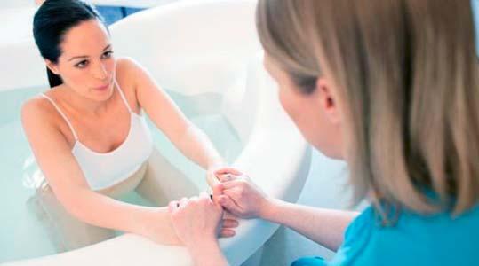 embarazada en bañera con doctora preparandose para el parto en el agua